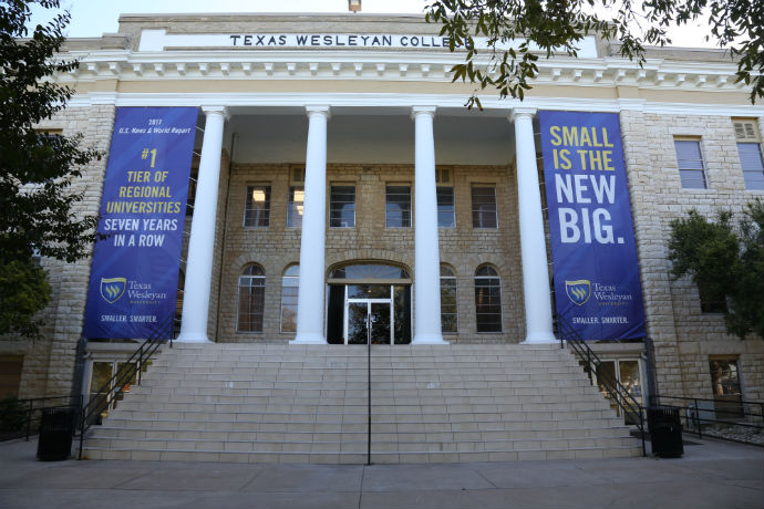 Outside view of Oneal-Sells Administration building at Texas Wesleyan. Displayed on the building are banners saying