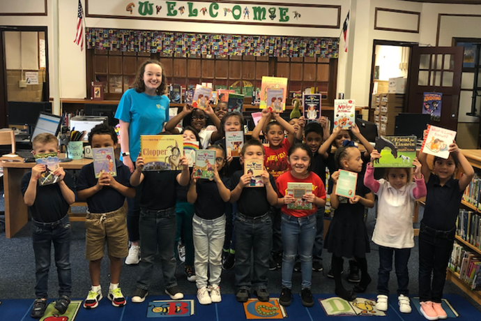 Photo of Fort Worth elementary school students receiving books from a book drive.