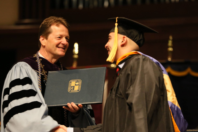 A photo of TXWES President Frederick G. Slabach handing a diploma to a graduate during Fall 2018 Commencement.