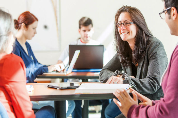 Image of teacher talking with students