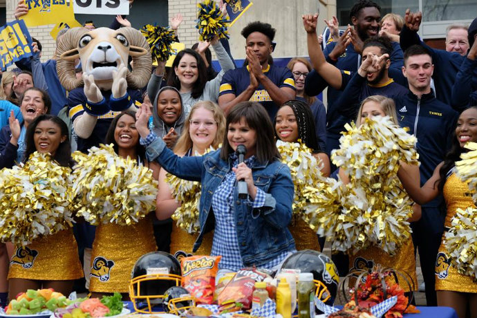 Photo of WFAA reporter Paige Smith during live broadcast of 'Good Morning Texas' from campus. Texas Wesleyan cheerleaders, staff and students are also pictured.