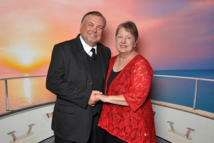 Photo of a man and woman in front of a cruise backdrop