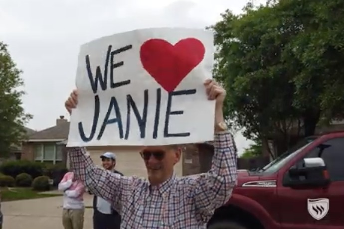 Photo of Professor Joe Brown honoring alumnae Janie Faris with a sign that says We Love Janie.