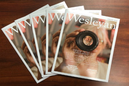 Set of Wesleyan magazine issues spread out on a desk