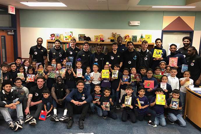 A group photo of first graders from Alice Contreras Elementary and the 2018-19 Texas Wesleyan Men's Basketball team. The students are holding their favorite books.