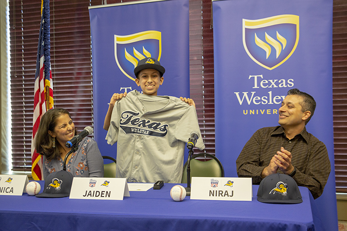 7th grader Jaiden Mehta holds up his jersey at his signing day event in the Baker Building