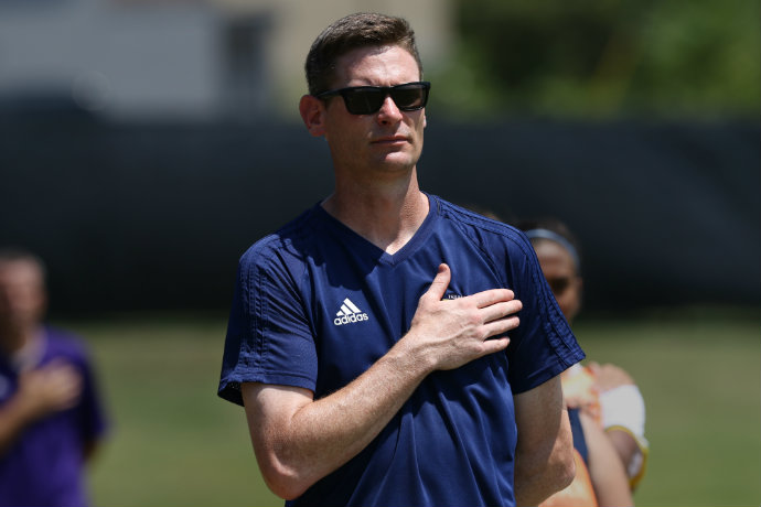 Head coach of Women's Soccer Josh Gibbs is pictured with his hand over his heart during the national anthem before a soccer match.