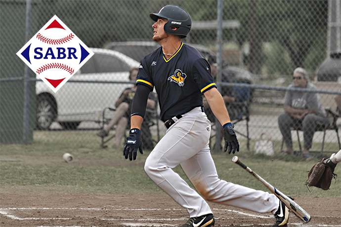 Menedez looks a the ball after he swings his bat. The SABR logo is also pictured