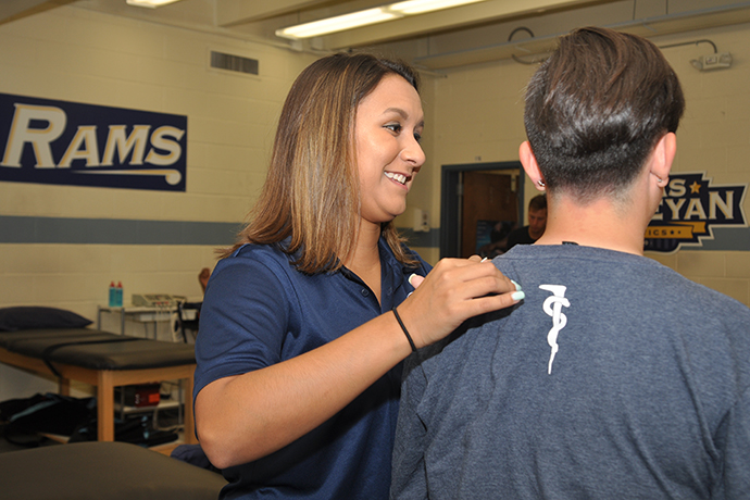Breanne Zuniga helps a student in the Texas Wesleyan athletic training room.
