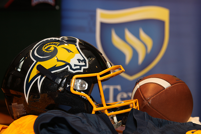 A Texas Wesleyan football helmet and football are displayed. The Texas Wesleyan shield is pictured in the background.