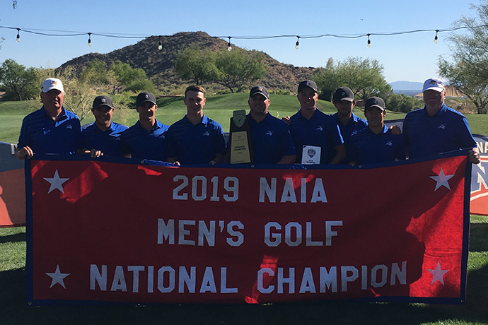Photo of the TXWES men's golf team with their 2019 national championship banner.