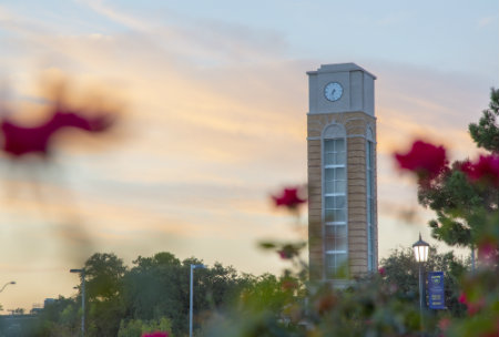 Picture of clock tower with flowers off to the peripheral