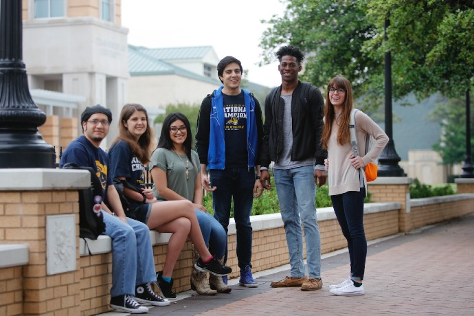 Students sit together in a group along Rosedale near Canafax Clock Tower and smile to the camera.