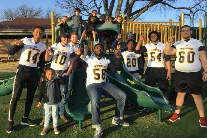 Photo of Texas Wesleyan football players taking part in a community service project with students at Temple Christian School in Fort Worth.