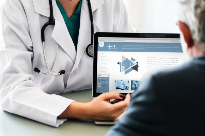 picture of doctor showing patient information on computer