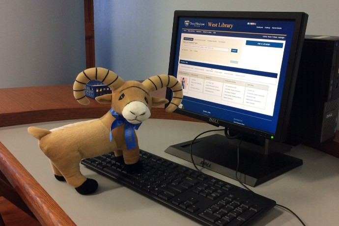 University Ram Mascot posing by a Library Computer
