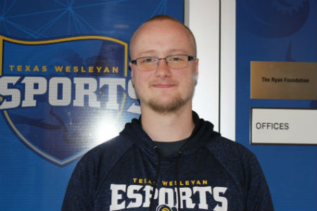 Young male college student stands in front of a door with the Texas Wesleyan esports logo on it