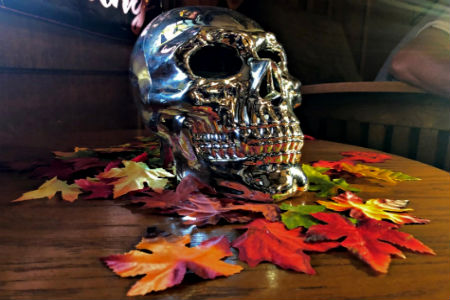 A silver skull sitting on a wooden table with fake leaves strewn about