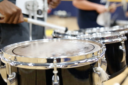 Student playing drums at basketball game