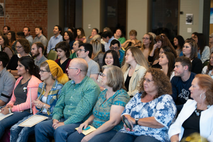 Photo of an audience sitting in rows at presentation listening