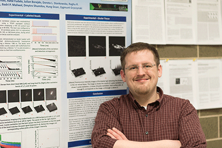 Dr. Ryan Rich stands in front of his research poster.