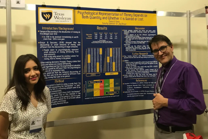 Photo of Texas Wesleyan psychology student Maria Perez and Jay Brown, professor of psychology with Maria's presentation at Undergraduate Research Day in Austin.