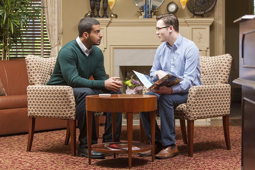 Admissions and Aid - Scholarship & Aid, a counselor helping out a young man figure out his life