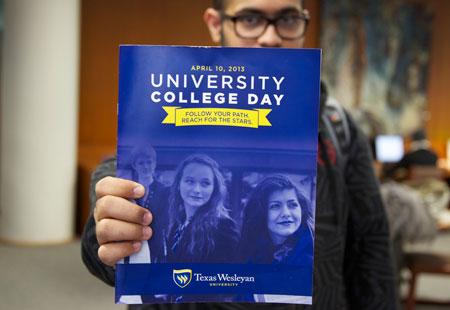 Texas Wesleyan male student holding a University College Day magazine