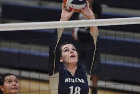 Volleyball player Katherine Rosenbusch spikes ball over the net